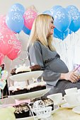 Pregnant Woman sitting down at a Baby Shower