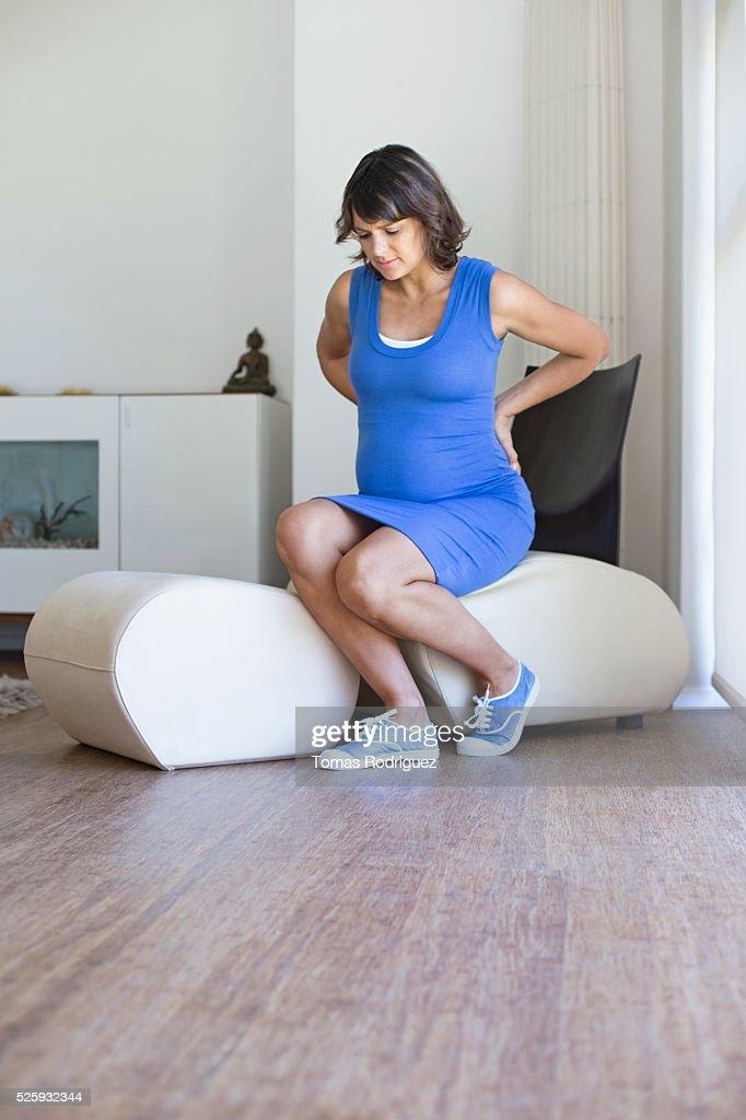 Pregnant woman sitting in chair : Foto de stock