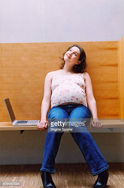 Pregnant Woman Sitting on Bench with Laptop