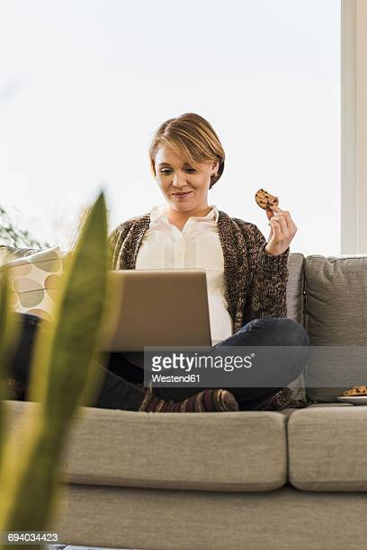 Pregnant woman sitting on couch eating a cookie and using laptop