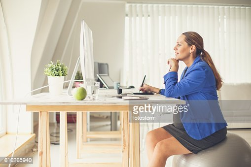 Pregnant woman sitting on fitness ball at office : Stock Photo