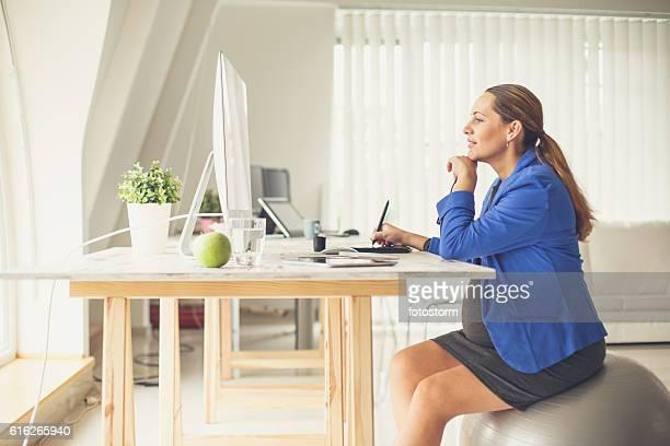 Pregnant woman sitting on fitness ball at office