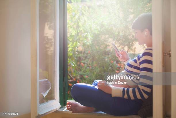 Pregnant woman sitting on window sill, relaxing with music