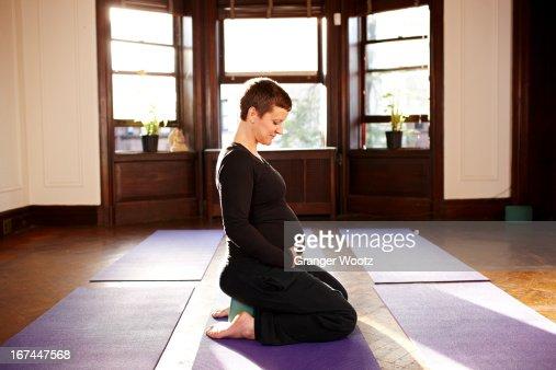 Pregnant woman sitting on yoga mat : Stock Photo