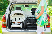 Pregnant woman standing beside opened car trunk. Parts of baby carriage. Preparing to become parent for future child. Things transportation. Green outdoor nature and sunny summer day atmosphere.