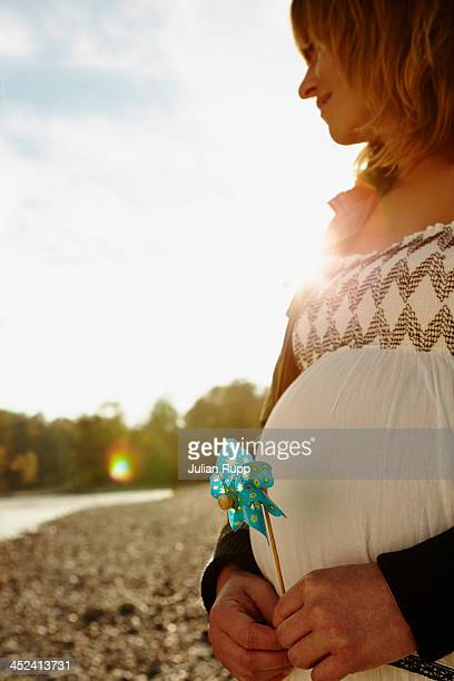 Pregnant woman standing beside river holding windmill
