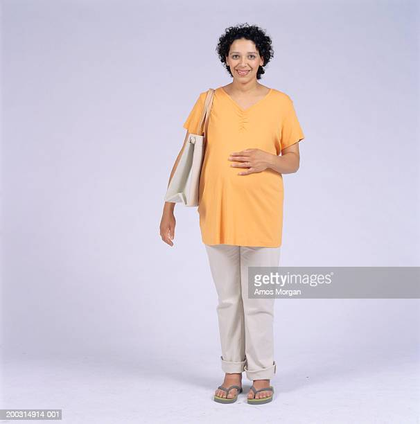Pregnant woman standing in studio, portrait