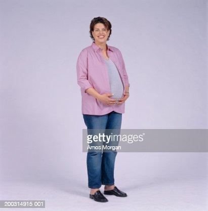 Pregnant woman standing in studio, portrait