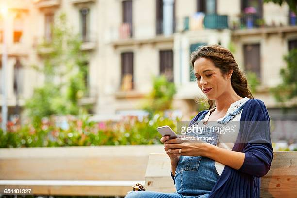 Pregnant woman text messaging in park