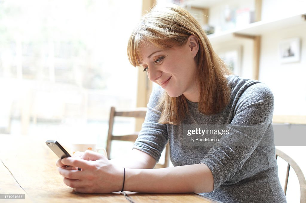 Pregnant woman texting on phone : Stock Photo