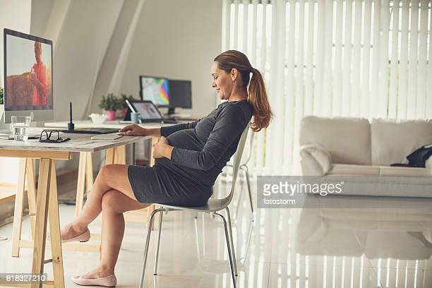Pregnant woman touching her belly in the office