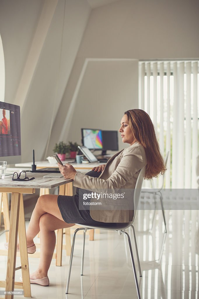 Pregnant woman typing on cellphone in office : Stock Photo