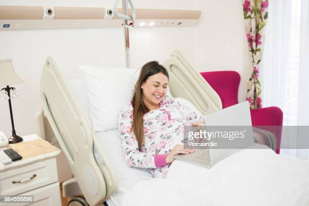 Pregnant Woman Using Laptop At Hospital