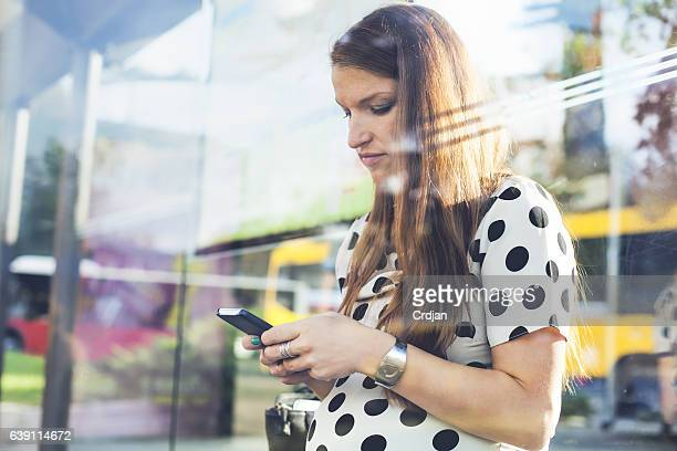 Pregnant woman using phone on station.