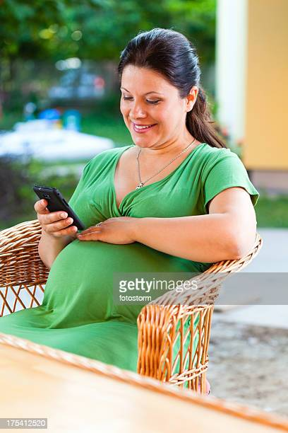 Pregnant woman using smart mobile phone outdoors