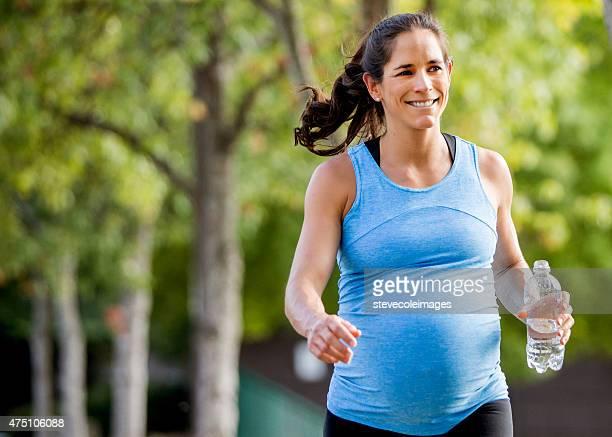 Femme enceinte heureuse, marcher et porter une bouteille d'eau.
