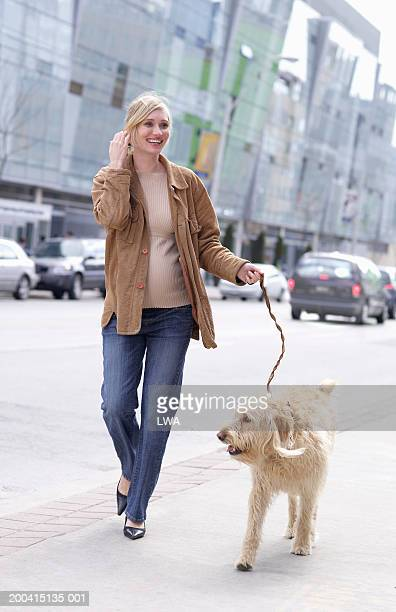 Pregnant woman walking dog, smiling