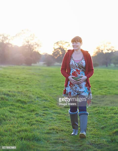 Pregnant woman walking in countryside.
