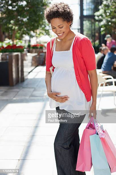 Pregnant woman walking with shopping bags