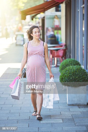 A pregnant woman walks with her shopping