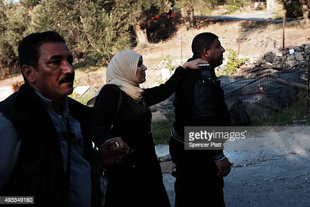 A pregnant woman who just arrived from on a raft from Turkey recieves help from her family as they make their way to a refugee reception center on...
