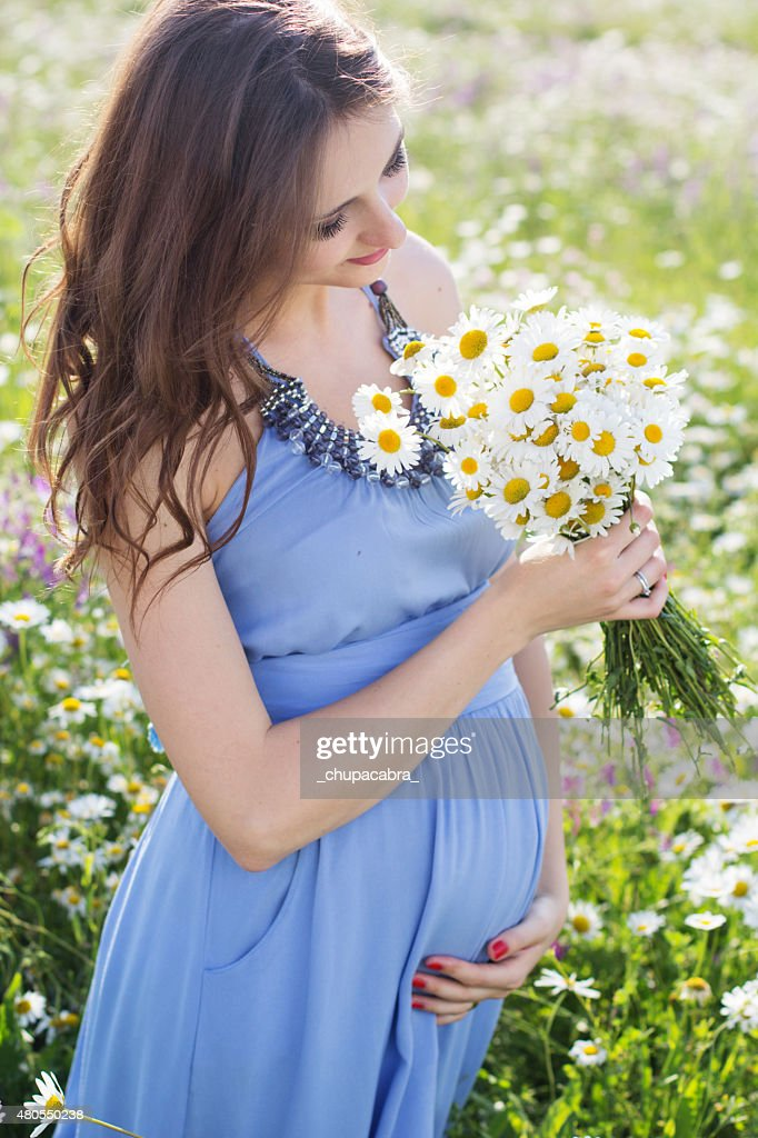 Pregnant woman with bouquet of daisy flowers : Stock Photo