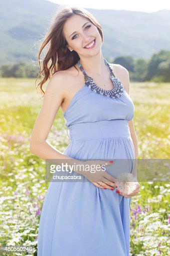 Pregnant woman with dandelion in hands : Stock Photo