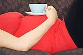 Pregnant woman with drink on sofa, mid section