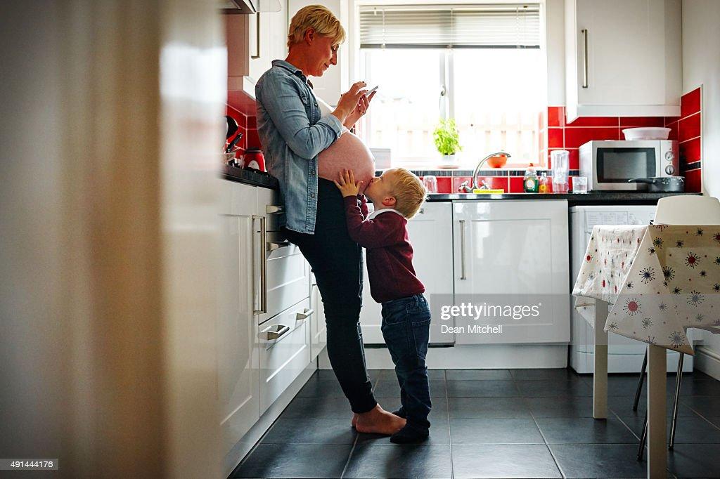 Schwangere Frau und ihr Sohn in der Küche : Stock-Foto