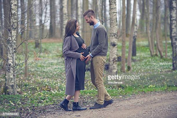 Schwangere Frau mit Mann stehend im Freien im Wald