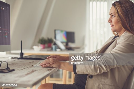 Pregnant woman working on the computer in office : Stock Photo