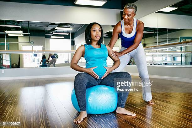 Pregnant woman working with yoga teacher in studio
