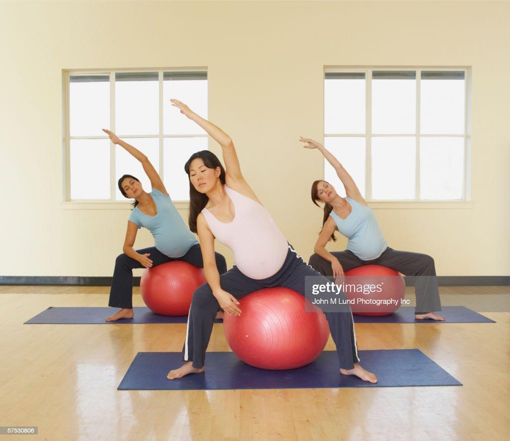 Balance Ball Exercises For Pregnancy: Pregnant Women Stretching On Exercise Balls Stock Photo