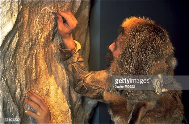 Prehistorical museum in Quinson France on May 29 2001 Paleolithic period a scene showing a Neanderthal man engraving a rock wall using a silexmade...