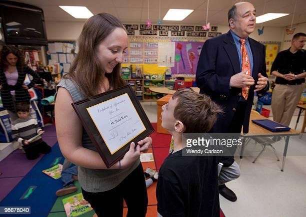 Prekindergartner teacher Holly Mora shows an appreciation plaque to student Alexander Parnas that was presented to her by children's author Alan Katz...