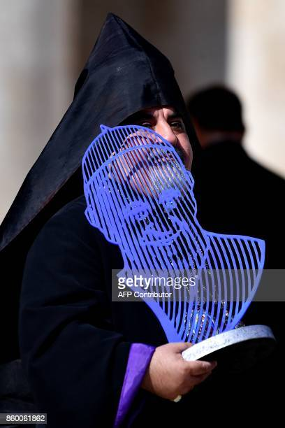 A prelate holds a statue depicting Pope Francis during his weekly general audience at StPeter's square on October 11 2017 in the Vatican / AFP PHOTO...