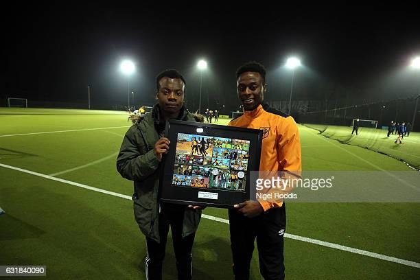 Premier League Kicks Hero Tresor Kalilwa recieves framed comic strip award from Hull City's Moses Odubajo at the KCOM astro pitches on January 16...