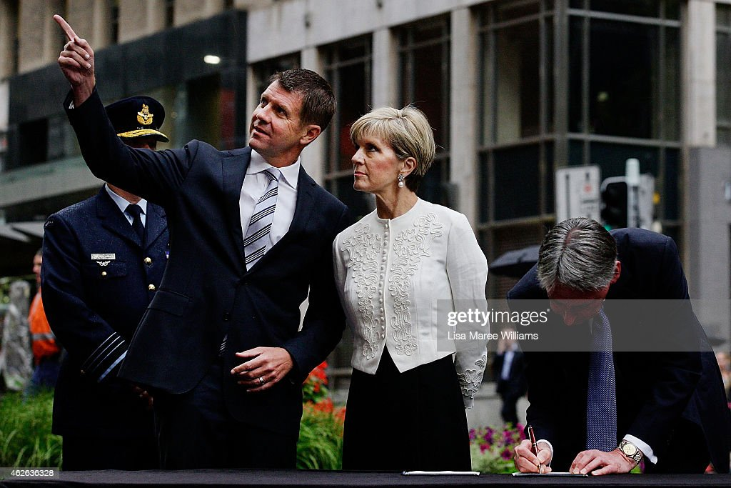 NSW Premier Mike Baird points something out to Australian Minister for Foreign Affairs Julie Bishop as UK Secretary of State for Foreign and Commonwealth Affairs, Philip Hammond signs the Lindt Cafe Siege Condolence Book at Martin Place on February 2, 2015 in Sydney, Australia. Philip Hammond, the Secretary of State for Foreign and Commonwealth Affairs and the Secretary of State for Defence, Michael Fallon, are currently in Australia for the AUKMIN foreign affairs and defence meetings.