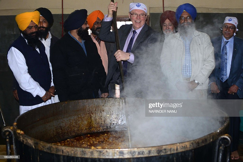 Premier of Manitoba Canada, Greg Selinger (C) assists in the preparation of food for a communal vegetarian meal, known as 'langar', during a visit to the Sikh Shrine Golden Temple in Amritsar on February 1, 2013. Selinger, along with a 16 member delegation, is on a visit to the country to consolidate bilateral relations between India and Canada.