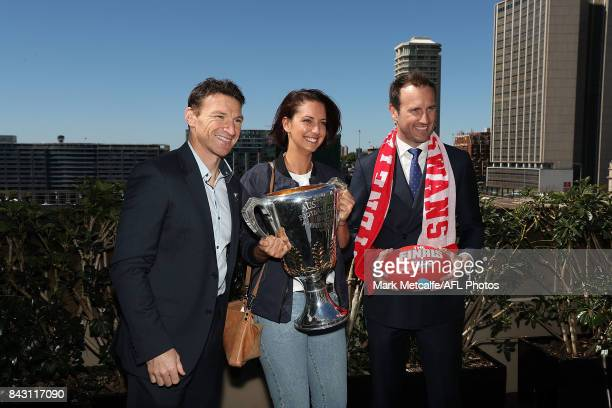 Premiership Cup Ambassador Brent Harvey and former Sydney Swans Premiership player Jude Bolton pose with the AFL trophy and a fan during the AFL...