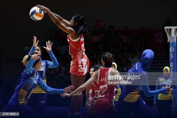 Premila Hirubalan of Singapore makes a block during the women's netball gold medal match between Singapore and Malaysia at the OCBC Arena Hall during...