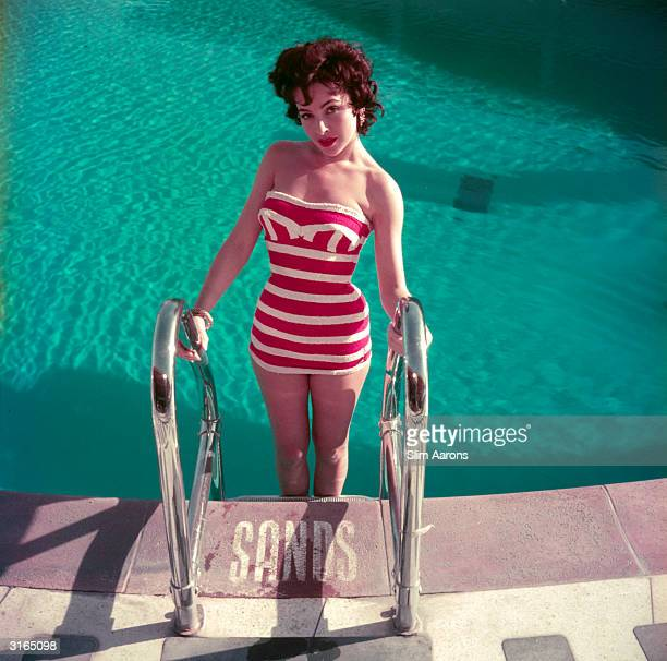Austrian actress Mara Lane posing by the pool at the Sands Hotel Las Vegas in a red and white striped bathing costume