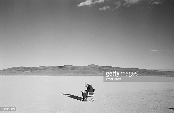 Director John Huston sitting alone during the filming of 'The Misfits' on location in the Nevada Desert