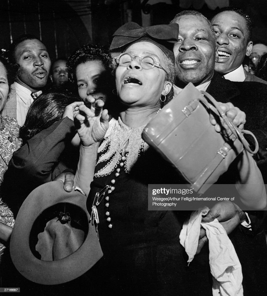 Premium Rates Apply. A woman is caught up in a religious ecstasy during a meeting in Harlem, New York. (Photo by Weegee (Arthur Fellig)/International Center of Photography/Getty Images)