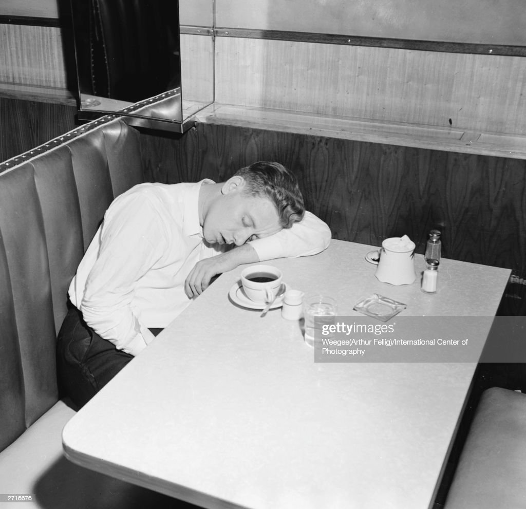 Premium Rates Apply. A young man falls asleep over a cup of coffee in a New York cafe. (Photo by Weegee (Arthur Fellig)/International Center of Photography/Getty Images)