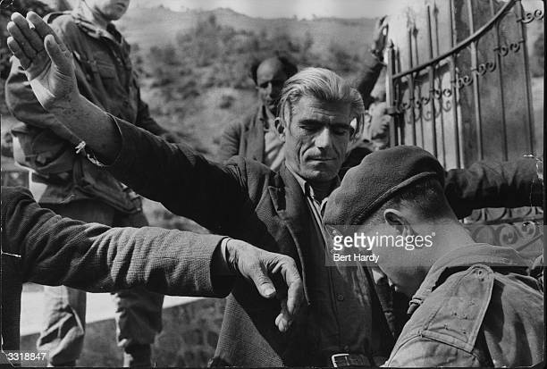 A suspected EOKA terrorist in the mountains of Cyprus is searched by a British soldier Original Publication Picture Post 8314 Terrorist Hunt In...