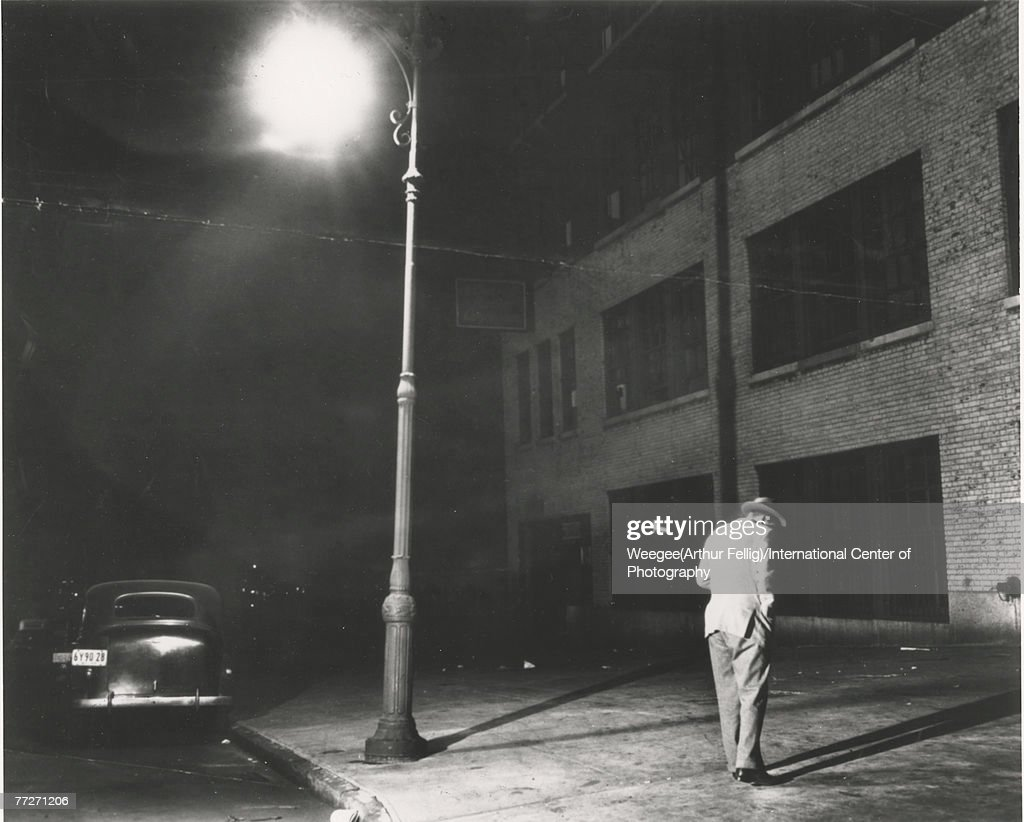Premium Rates Apply. As he stands under a lone streetlight, a man in a suit and hat glances down at the sidewalk, New York, New York, March 5, 1945. (Photo by Weegee(Arthur Fellig)/International Center of Photography/Getty Images)