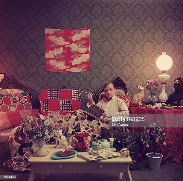 Premium Rates Apply Author Truman Capote relaxes with a book and a cigarette in his cluttered apartment Brooklyn Heights New York Original...