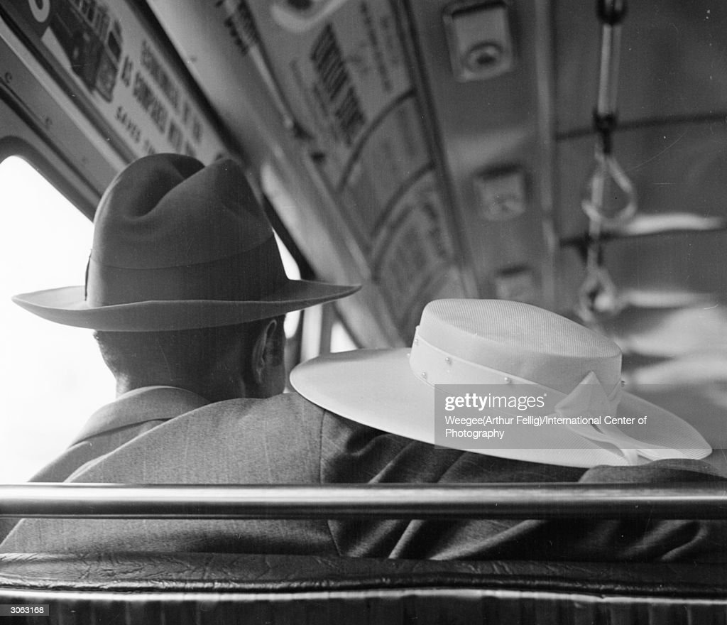A man puts his arm around his female companion during a bus journey. (Photo by Weegee(Arthur Fellig)/International Center of Photography/Getty Images)