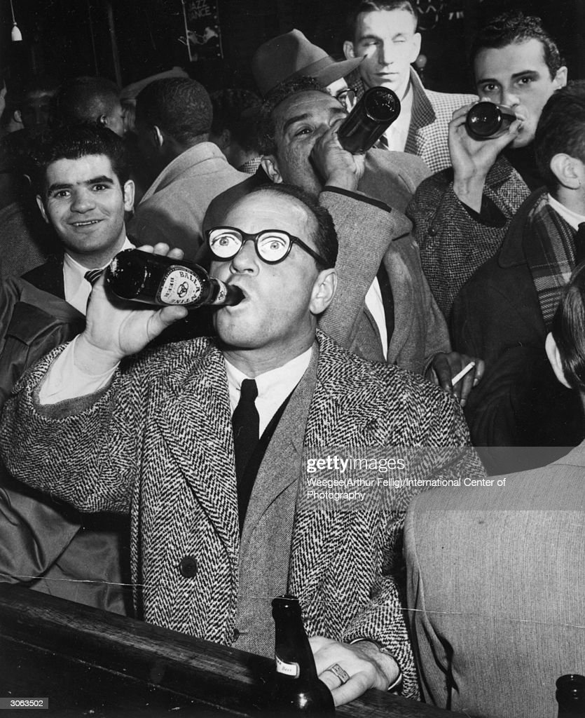 A man wearing comedy glasses downs a bottle of beer at a bar in 'The Village', New York City. (Photo by Weegee(Arthur Fellig)/International Center of Photography/Getty Images)